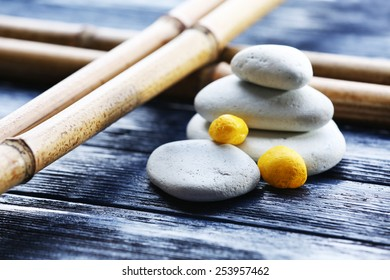 Spa stones with dry bamboo on wooden background