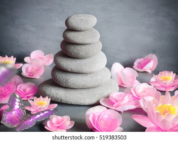 Spa stones with flower lily and butterfly on grey background