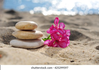 Spa stones with flower on sea beach
