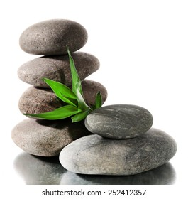 Spa stones with green leaves isolated on white