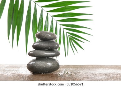 Spa stones with green leaves, isolated on white
