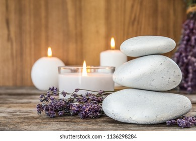 Spa stones with lavender flowers and candles on table