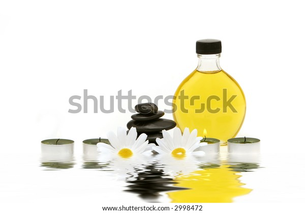 Spa stones, oil and candles isolated on white background