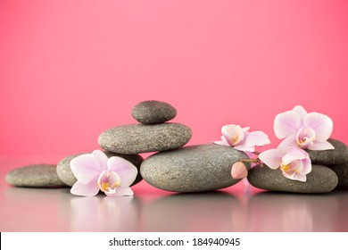 Spa stones on pink background with orchids.