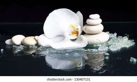 Spa stones with orchid flower on black background