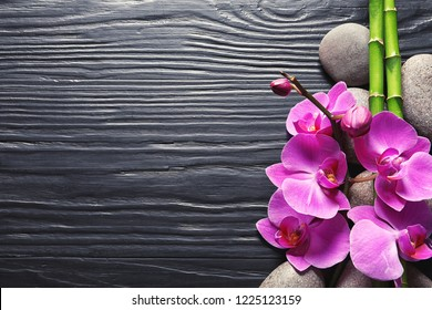 Spa stones with orchid flowers and bamboo on dark wooden background, top view. Space for text