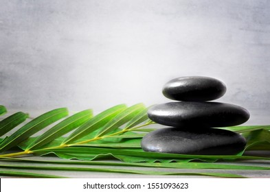 Spa stones with palm branch on light background. Space for text.