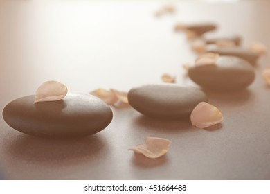 Spa stones with petals on grey background