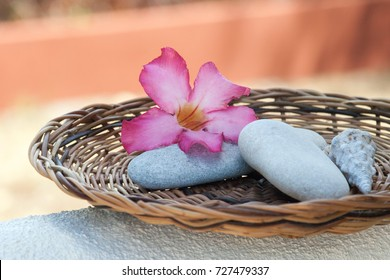 Spa stones with pink flower on the rattan plate used as spa ingredients