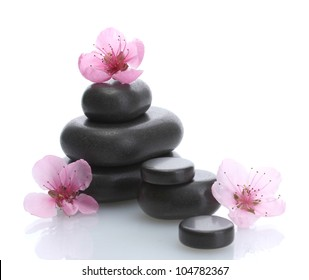 Spa stones and pink sakura flowers isolated on white