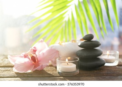 Spa stones with towel, candles, palm leaves and pink orchid on wooden background