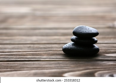 Spa stones with water drops on wooden background