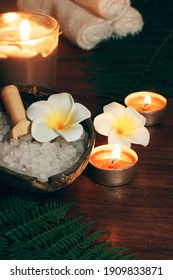 Spa style fern composition with burning candles and bath salt.