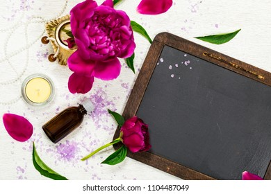 Spa Theme Objects Bath Salt, Fresh Purple Peony Flowers with Black Chalkboard Background Card Concept, Top View. Selective focus.