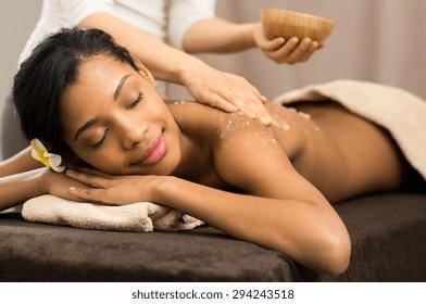 Spa-thérapeute appliquant du sel de gommage à une jeune femme au spa salon