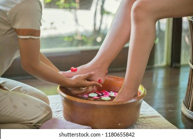 Spa therapy, female feet at spa procedure by therapist Women's feet soaked in a bowl with water and flower therapy