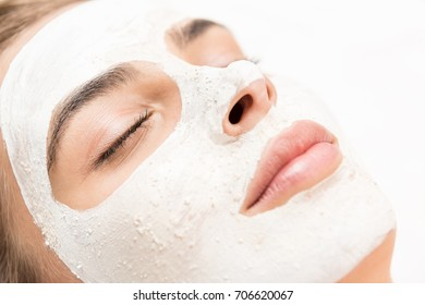 spa therapy for woman receiving facial mask, isolated on white