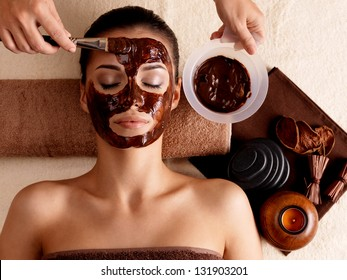 Spa therapy for young woman with cosmetic mask at beauty salon - indoors