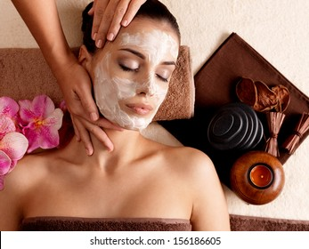 Spa therapy for young woman having  facial mask at beauty salon - indoors