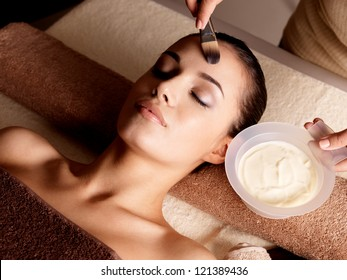 Spa therapy for young woman receiving facial mask at beauty salon - indoors