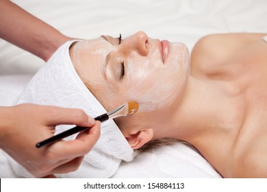 Spa therapy for young woman receiving facial mask at beauty salon