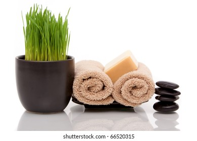Spa towel, soap and wheatgrass on white background