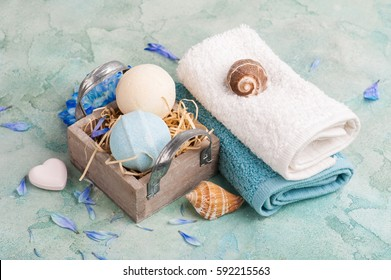 SPA treatment. Blue flowers and bath bombs on turquoise concrete background.