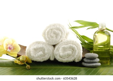 Spa treatment- bowl of towel and massage oil ,orchid, stacked stones and bamboo leaf