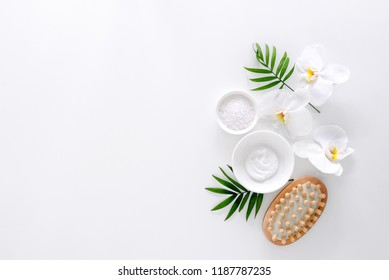 Spa treatment concept, flat lay composition with natural cosmetic products and massage brush, view from above, blank space for a text