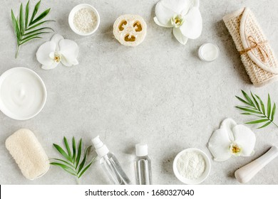 Spa treatment concept. Natural/Organic spa cosmetics products, sea salt, massage brush, tropic palm leaves on gray marble table from above. Spa background with a space for a text, flat lay, top view - Shutterstock ID 1680327040