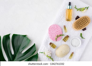 Spa treatment on white background with bamboo stalk and green palm leaves, flat lay. Top view of beauty bath background for body care and wellness