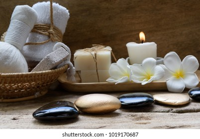 Spa and treatment setting with ,zen stone,candle light,towels,coconut soap and frangipani flowers on wooden table  background