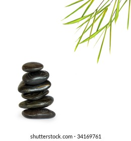 Spa treatment stones in perfect balance with bamboo leaf grass, over white background.
