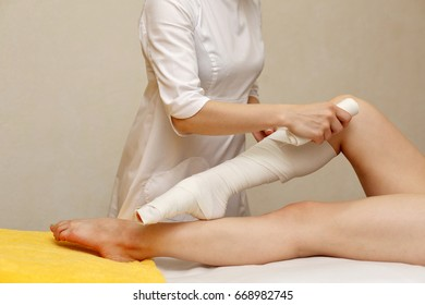 Spa treatment. STYX wrap. Anti-cellulite treatment. The cosmetologist wraps the feet of the client.
