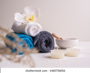 Spa treatment, towels and tealights on a white background, orchid blossom, massage, aromatherapy