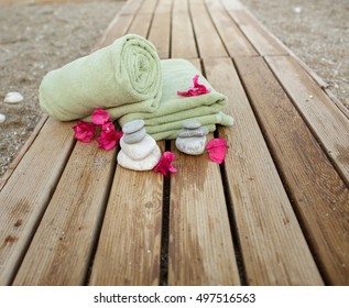 Spa treatment treatment of tropical flowers towel and zen stones on wooden walkway. Zen stone and green towels at sandy beach at sunset closeup