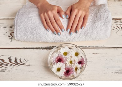 Spa treatments for hands. Manicure salon. Beautiful glass bowl with flowers.