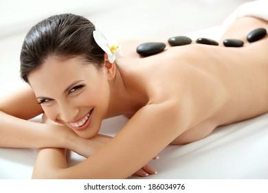 Spa Tretment. Beautiful Woman Getting Spa Hot Stones Massage in Spa Salon.