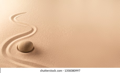 Spa wellness background of a zen meditation garden with sand and round stone. A nice curved line on sandy texture. Lots of copy space.