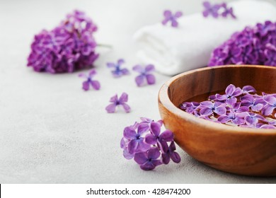 Spa and  wellness composition with perfumed lilac flowers water in wooden bowl and terry towel on gray stone background, aromatherapy