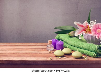 Spa and wellness concept with fresh towel, candles and flowers on wooden table with copy space