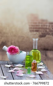 Spa and wellness concept: preparation of essential oil with pink roses, bottle of tincture and mortar on wooden board with all vintage wall