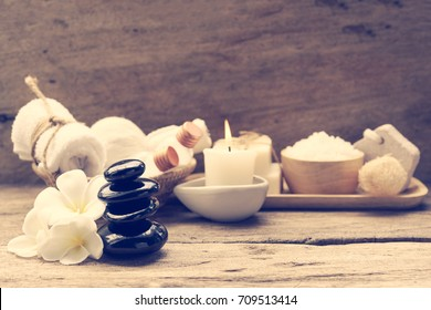 Spa wellness concept,white candle,milk soap,salt,towel,flowers and herbal massage ball on rustic wood table  background
