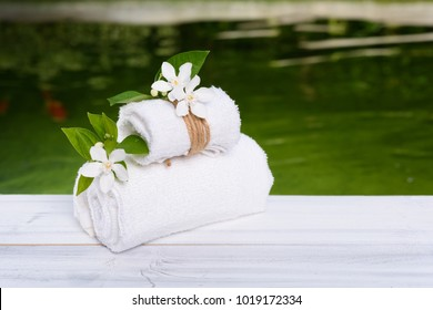 Spa wellness concept,white towels and beautiful flowers on white wood table with green pond background