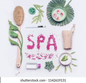 Spa or Wellness flat lay on white background. Body care and cellulite treatment tools. Natural brush for dry skin peeling or massage , cream and luffa sponge with flowers and tropical leaves, top view