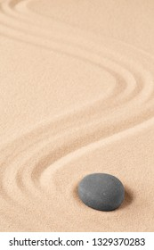 Spa wellness for inner life and spiritual health. Zen meditation stone for relaxation. Concept for purity balance and harmony. Background with raked sand and open copy space.