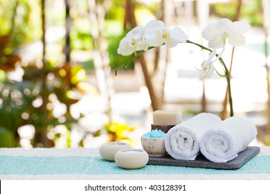 Spa and wellness massage setting Still life with candle, towel and stones Outdoor summer background with fresh white orchid Copy space