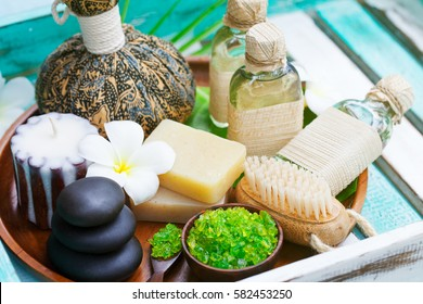 Spa and wellness massage setting. Still life with candle, towel and stones. Outdoor summer background.