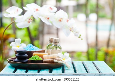 Spa and wellness massage setting. Still life with candle, towel and stones. Outdoor summer background. Copy space.