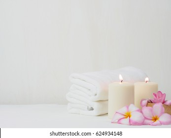 spa wellness set.beauty and fashion set on the white table.spa towel with candle and plumeria, tree on the white table.